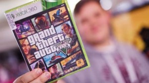 A-man-holds-up-his-copy-of-new-console-game-Grand-Theft-Auto-V-at-the-midnight-opening-in-London-AFP